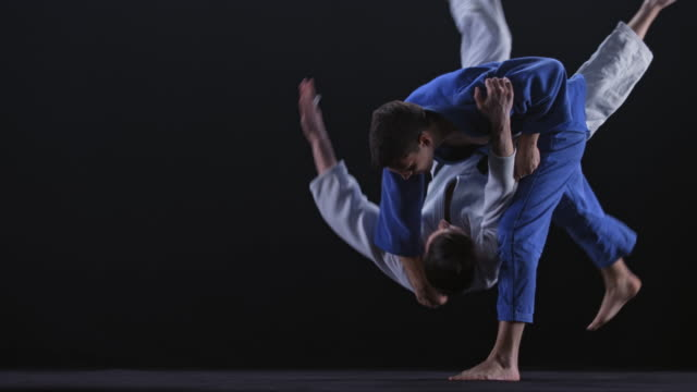 slo mo ld judoka in blue outfit grabbing his opponent and throwing him on the floor - contest stock videos & royalty-free footage