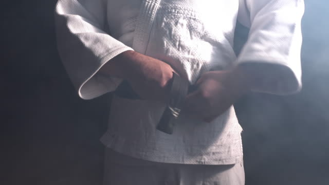 Judokas Fighter tying black belt