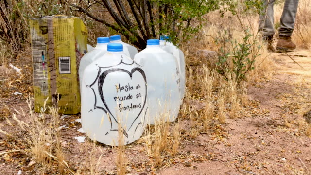 jugs of water for undocumented immigrants sits along migrant trails after being delivered by volunteers for the humanitarian aid group no more deaths... - human face video stock e b–roll