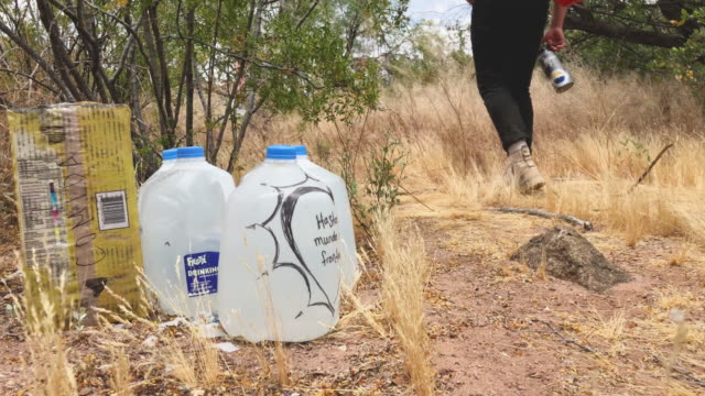jugs of water for undocumented immigrants sits along migrant trails after being delivered by volunteers for the humanitarian aid group no more deaths... - jug stock videos & royalty-free footage