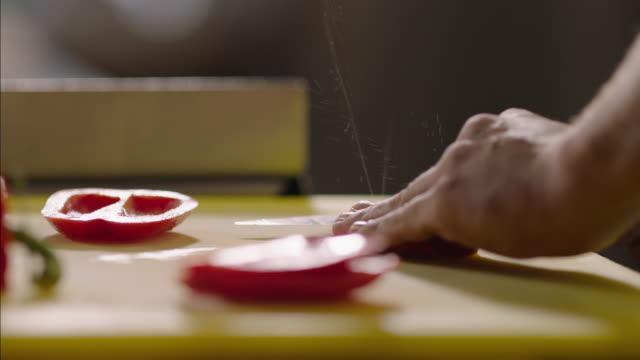 vídeos y material grabado en eventos de stock de juice sprays as skilled hands cut red pepper in restaurant kitchen - picar preparar comida
