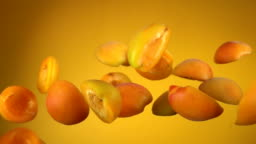 Juicy apricot halves bounce on yellow background