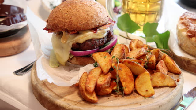 juicy burger with cheese and bacon served with baked potatoes - cheeseburger stock videos & royalty-free footage