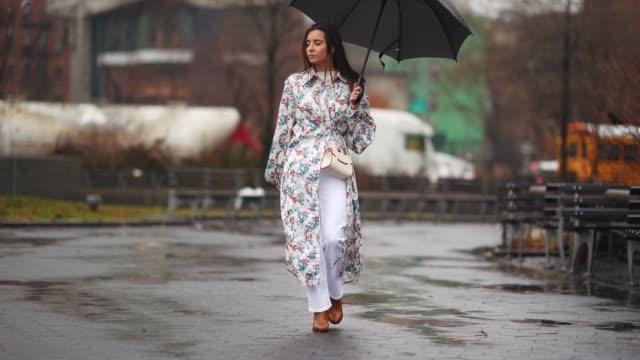 vídeos de stock e filmes b-roll de julia comil wears a colored floral print long coat, a white bag, white pants, brown leather shoes, an umbrella, during new york fashion week women's... - chapéu