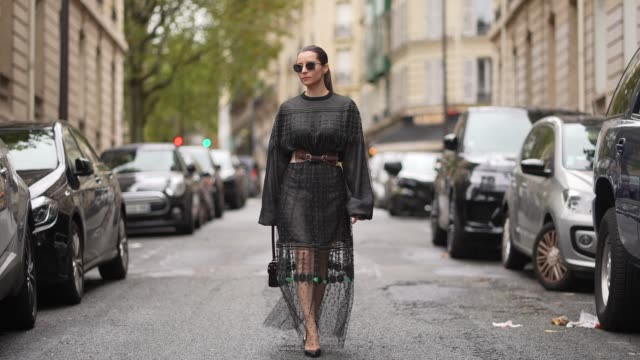 julia comil wears a longchamp black and green dress with mesh, lace and puff sleeves, a leather crocodile pattern longchamp bag, a brown sandro... - scarpe video stock e b–roll