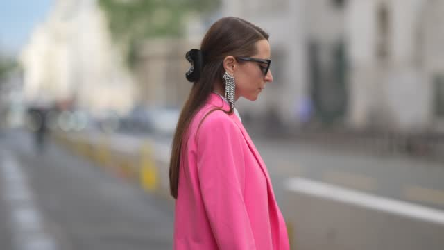 vídeos y material grabado en eventos de stock de julia comil wears black sunglasses, a rhinestone pendant earring, gold earrings, a white shirt, a pink oversized blazer jacket, a gray leather... - pantalón corto