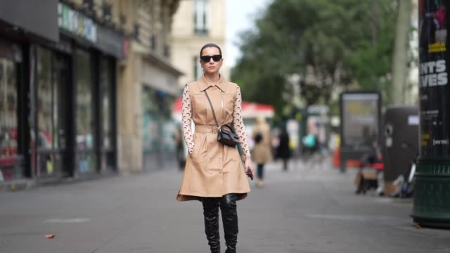 julia comil wears sunglasses, earrings, a beige sleeveless leather trench coat, a black leather jacquemus bag, a pale pink marine serre printed logo... - sleeveless top stock videos & royalty-free footage