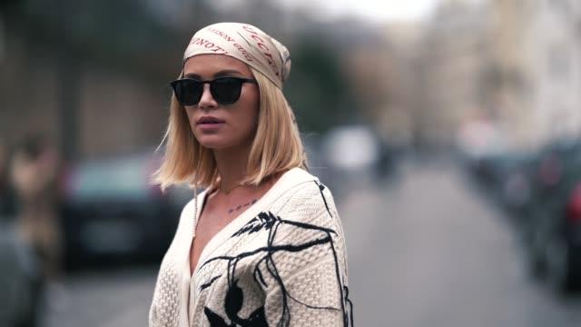 Julia Kuczynska 'Maffashion' wears a bandanna from Gucci a white wool jacket with print depicting nature white pants a Prada bag white boots outside...