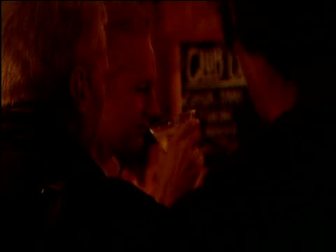Julian Assange the founder of Wikileaks stands drinking in a pub having been released on bail