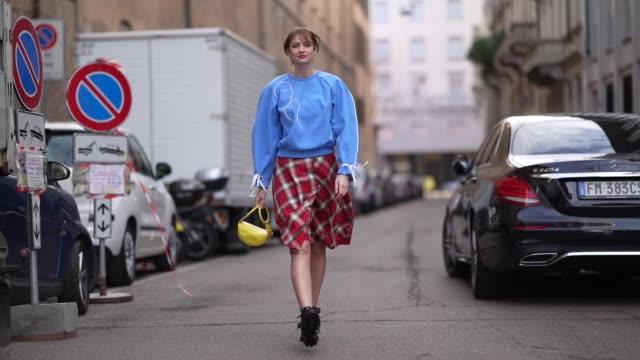 vídeos y material grabado en eventos de stock de julie ianc wears a blue pullover, a red checked skirt, a yellow bag, black shoes, outside max mara, during milan fashion week fall/winter 2020-2021... - falda