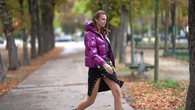stockvideo's en b-roll-footage met julie ianc wears a lustrous fuchsia hooded puffer jacket, a black bag, a black mini skirt, black crocodile pattern flat boots, outside margiela,... - hoofddeksel