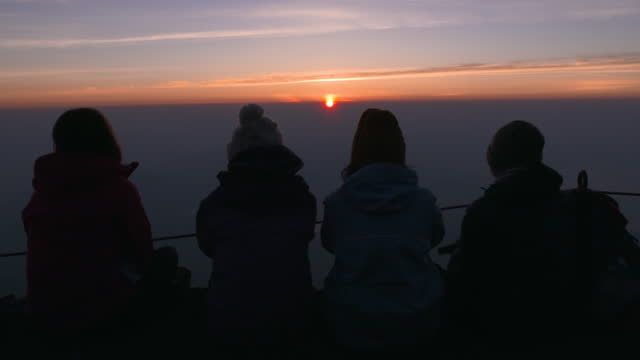 july 10 back shot of climbers watching sunrise from mt fuji - mt fuji stock videos & royalty-free footage