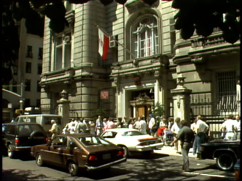 vidéos et rushes de july 11, 1985 small crowd and cars in front of government building flying polish flag / warsaw, poland - varsovie