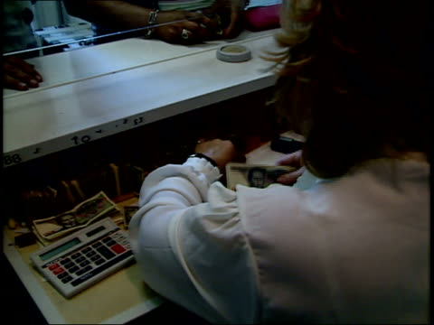 July 12 1989 TU Cashier at currency exchange behind glass window sorting money counting bills for customer / Warsaw Poland