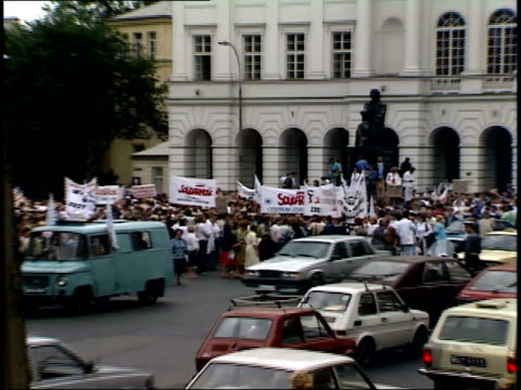 vídeos de stock, filmes e b-roll de july 12, 1989 crowd at presidential palace standing and holding banners for solidarity, traffic moving on street / warsaw, poland - 1980 1989