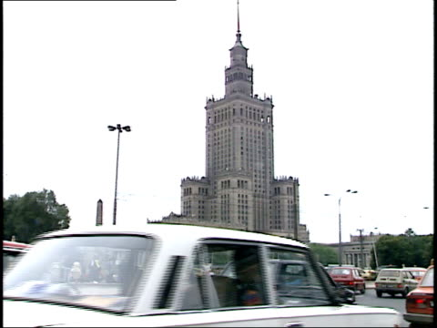 july 12 1989 montage cars and bus driving through dmowski roundabout tram waiting on side of road / warsaw poland - 1980 1989 video stock e b–roll