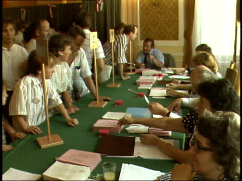 vídeos de stock, filmes e b-roll de july 12 1989 montage prospective voters in customs building registering to vote with their passports a father hugging his sons / warsaw poland - enfoque de objeto sobre a mesa
