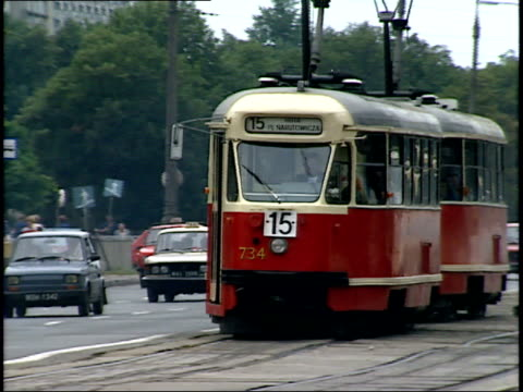 july 12 1989 ws red electrical trams driving along roadway / warsaw poland - anno 1989 video stock e b–roll
