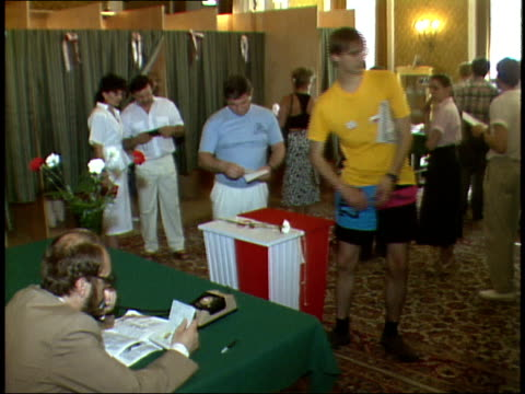 july 12, 1989 voters slipping completed ballots into ballot box decorated with red and white carnations / warsaw, poland - röstsedel bildbanksvideor och videomaterial från bakom kulisserna