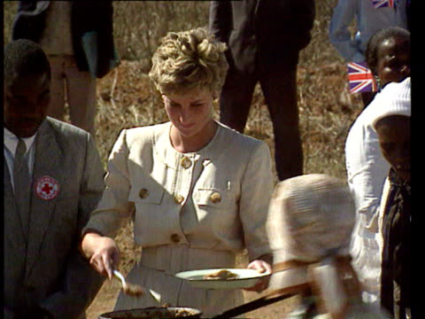 stockvideo's en b-roll-footage met july 12 1993 film montage ms zi princess diana serving food to hungry people at red cross food station/ ms diana sitting with children as they eat/... - handen in een kommetje