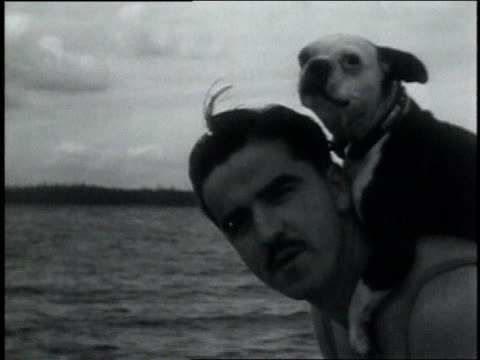 July 13, 1931 MONTAGE Man diving into lake with dog on shoulders / Seattle, Washington, United States