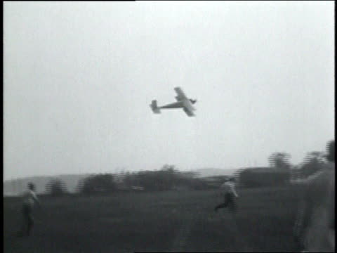 july 13, 1931 montage young men flying a large model bi-plane as crowd watches / ws plane crashing into ground / dayton, ohio, united states - 1931 bildbanksvideor och videomaterial från bakom kulisserna