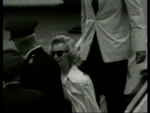 vídeos de stock e filmes b-roll de july 14 1956 film montage ms marilyn monroe and arthur miller exiting plane and walking down steps/ marilyn monroe and arthur miller entering... - fato completo