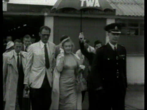vídeos de stock e filmes b-roll de july 14 1956 film montage ms pan marilyn monroe and arthur miller walking across rainy airport grounds surrounded by people/ london england/ audio - fato completo
