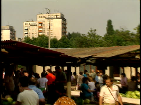 july 15 1989 ws shoppers browsing an outdoor market with residential complex and trees looming in the background / warsaw poland - 1980 1989 video stock e b–roll