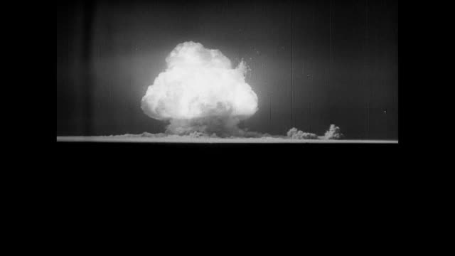 vídeos de stock e filmes b-roll de gadget' nuclear bomb exploding round fireball moving upward pulling earth up after. alamogordo bomb range the atomic age. - arma nuclear