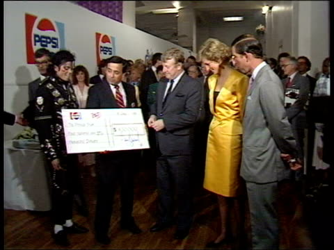 july 16, 1988 film montage michael jackson and pepsi executives presenting princess diana and prince charles with large donation for prince's trust/... - プリンスズトラスト点の映像素材/bロール