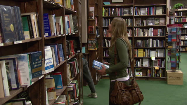 july 16, 2009 shopper browsing books while store clerk is placing books on shelf in book store / denver, colorado, united states - archivista video stock e b–roll