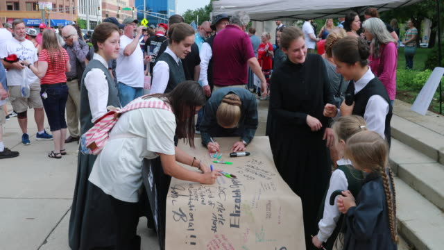 """july 19, 2020 - indianapolis, indiana usa: protesters sign a banner to leave on the doors of the statehouse for the indiana governor during the """"we... - july stock videos & royalty-free footage"""