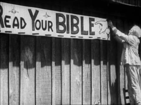 b/w july 1925 man hammering up read your bible sign / scopes trial tennessee / newsreel - 1925 stock videos & royalty-free footage