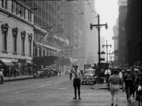 stockvideo's en b-roll-footage met july 1938 b/w ws tu busy intersection, large hotel in background, traffic cop and pedestrian in foreground / chicago, illinois, usa - 1938
