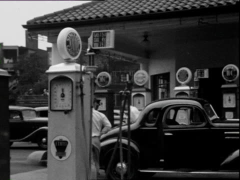 stockvideo's en b-roll-footage met july 1938 b/w montage gas station (wolfs head oil) with nice car, car owner smoking pipe, smiling into camera / chicago, illinois, usa - 1938