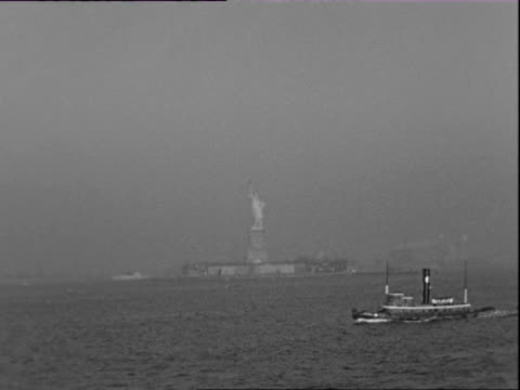 July 1938 B/W MONTAGE Moving toward Statue of Liberty and NYC harbor, downtown Manhattan skyline in mist / New York City, New York, USA