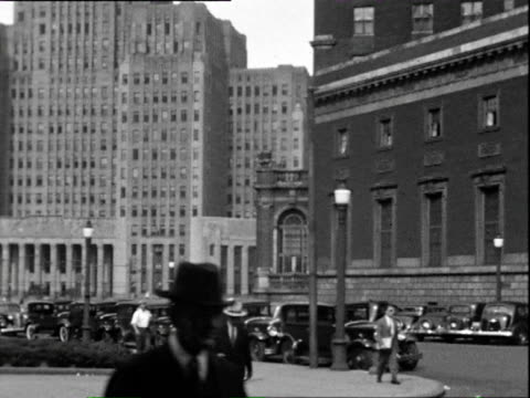 stockvideo's en b-roll-footage met july 1938 b/w ws pan tu street scene, parked cars in front of massive building / chicago, illinois, usa - 1938