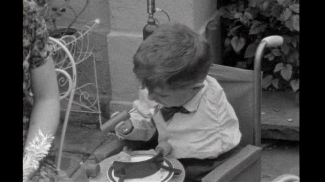 july 1963: b/w young boy with artificial arms feeding himself - thalidomide stock videos & royalty-free footage
