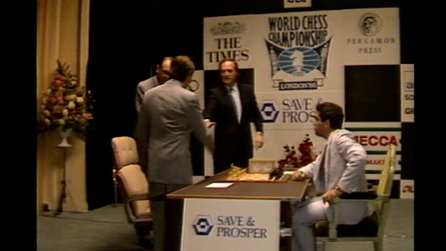 stockvideo's en b-roll-footage met park lane hotel photography*** kasparov sitting at chess table as joined by karpov and both shake hands reporter picking up chess piece reporter to... - schaakstuk