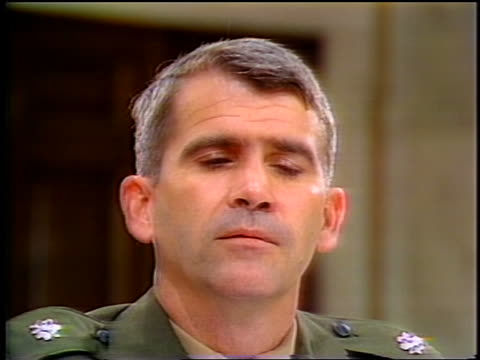 july, 1987 close up oliver north starting to talk then looking down during iran-contra hearings - 1987 bildbanksvideor och videomaterial från bakom kulisserna