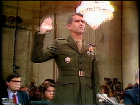 july, 1987 slight zoom in oliver north with hand raised being sworn in during iran-contra hearings - 宣誓点の映像素材/bロール