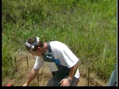 July 1997 WS Princess Diana walking on footpath surrounded by land mine signs/ MS Man pointin to mine in dirt/ CU mine in dirt/ MS Diana walking/ CU...