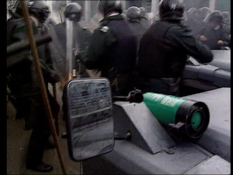 july 1998 gv group of ruc officers in riot gear standing across street as molotov cocktail lands amongst them and they try to stay clear of the... - molotov cocktail stock videos and b-roll footage