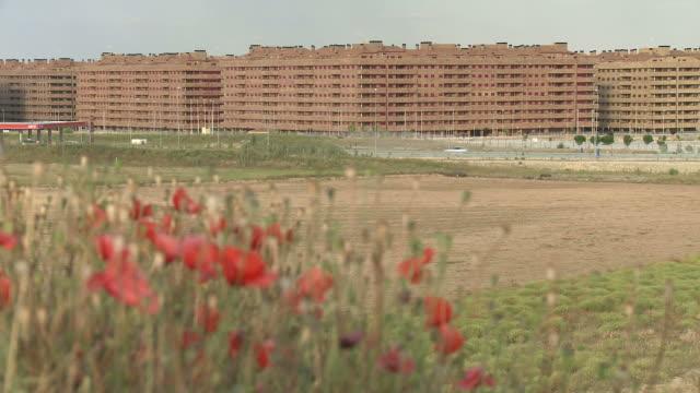 vídeos y material grabado en eventos de stock de july 2, 2010 flowers growing in field in front of high-rise apartment buildings / sesena nuevo, toledo, spain - formato buzón