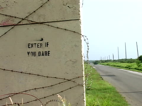 "july 2005 close up ""enter if you dare"" sign stenciled on cement near road/ guantanamo bay - western script stock videos & royalty-free footage"