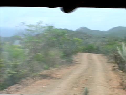 july 2005 medium shot through windshield of humvee driving down dirt road/ guantanamo bay - humvee stock videos & royalty-free footage