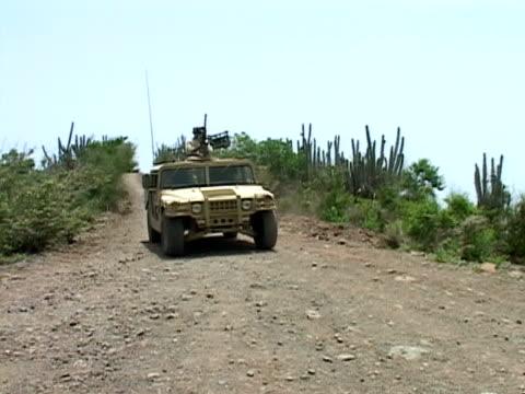vídeos de stock, filmes e b-roll de july 2005 medium shot us soldiers driving down road in armed military vehicle/ guantanamo bay - uniforme militar