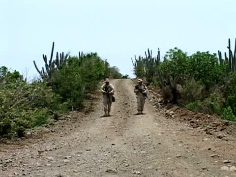 july 2005 wide shot us soldiers walking down path/ guantanamo bay - fianco a fianco video stock e b–roll