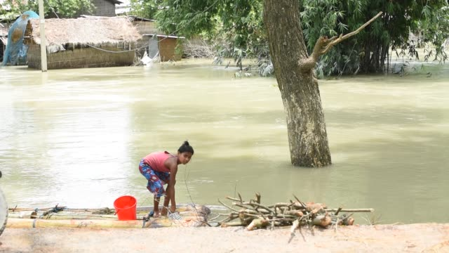 july 2020. a girl washing clothes on a banana tree raft in the flooded area, due to monsoon rains, in a flood affected village morigaon district of... - india stock videos & royalty-free footage